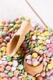 Pila de caramelos redondos coloridos con la taza y la cuchara de madera Foto de archivo