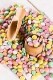 Pila de caramelos redondos coloridos con la taza y la cuchara de madera Imagen de archivo libre de regalías