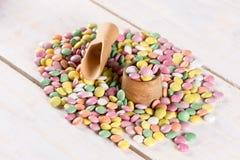 Pila de caramelos redondos coloridos con la taza y la cuchara de madera Fotografía de archivo