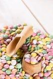 Pila de caramelos redondos coloridos con la taza y la cuchara de madera Fotografía de archivo libre de regalías