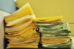 Pila de carpetas amarillas en la tabla Imágenes de archivo libres de regalías