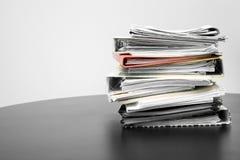 Pila de carpetas y de documentos en la tabla de la oficina Fotos de archivo libres de regalías