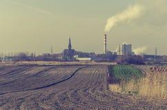 Pila de chimenea que fuma de una central eléctrica cerca de un campo de granja fotografía de archivo libre de regalías