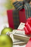 Pila de cientos billetes de dólar con el arco cerca de los ornamentos de la Navidad Imágenes de archivo libres de regalías