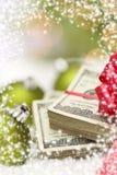 Pila de cientos billetes de dólar con el arco cerca de los ornamentos de la Navidad Imagenes de archivo