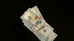 Pila de cientos billetes de dólar que caen en la tabla almacen de video
