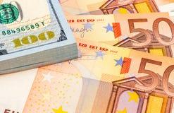 Pila de cientos billetes de dólar americanos y de billetes de banco euro Imagenes de archivo