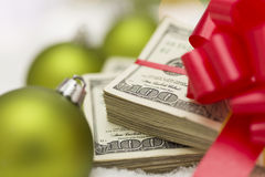 Pila de cientos billetes de dólar con el arco cerca de los ornamentos de la Navidad Imagen de archivo libre de regalías