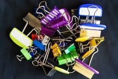 Pila de clips coloridos de la carpeta en un fondo negro Fotografía de archivo libre de regalías