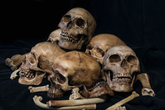 Pila de cráneos y de huesos en tela negra Imágenes de archivo libres de regalías
