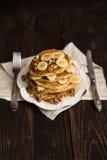Pila de crepes con la miel, el plátano y las nueces Fotografía de archivo