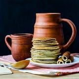 Pila de crepes con un jarro y una taza de la arcilla Fotos de archivo libres de regalías