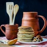 Pila de crepes, de jarro de la arcilla y de taza con los cubiertos de madera Fotos de archivo libres de regalías