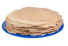 Pila de crepes deliciosas en la placa azul aislada con el fondo blanco Fotos de archivo