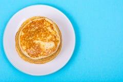 Pila de crepes deliciosas frescas en la placa blanca en backgro azul Fotografía de archivo libre de regalías
