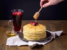 Pila de crepes hechas en casa sabrosas con los arándanos y Honey Cup de la mano de madera de Famale del fondo del té de las bayas Imagenes de archivo