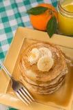 Pila de crepes para el desayuno con el zumo de naranja Fotos de archivo