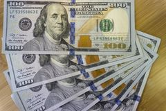Pila de Crolled de 100 nuevos billetes de dólar en fondo de madera foto de archivo