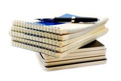 Pila de cuadernos aislados en un blanco Imagen de archivo libre de regalías