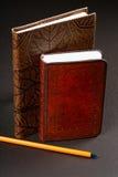Pila de cuadernos en cubiertas del cuero y un lápiz fotos de archivo libres de regalías