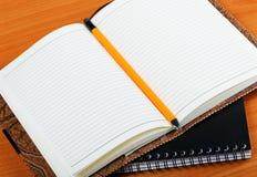 Pila de cuadernos en cubiertas del cuero y un lápiz fotografía de archivo libre de regalías