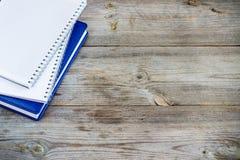 Pila de cuadernos en la tabla de madera Imagen de archivo