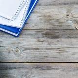 Pila de cuadernos en la tabla de madera Imagen de archivo libre de regalías