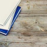 Pila de cuadernos en la tabla de madera Imagenes de archivo