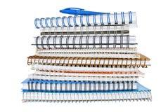 Pila de cuadernos espirales con una pluma azul Imágenes de archivo libres de regalías