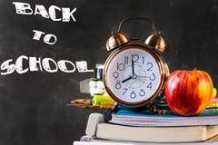 Pila de cuadernos, libros de texto, cojines, lápices, fuentes con la manzana roja del despertador en el top Pizarra negra Fotografía de archivo