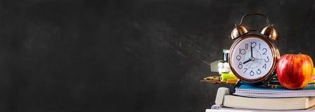 Pila de cuadernos, libros de trabajo, cojines, lápices, fuentes con la manzana roja del despertador en el top Pizarra negra De nu Fotografía de archivo libre de regalías