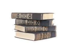 Pila de cuatro libros en una cubierta de tela negra aislada Fotos de archivo