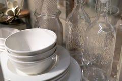 Pila de cuenco, de placa y de botellas de cerámica blancos Imagen de archivo libre de regalías
