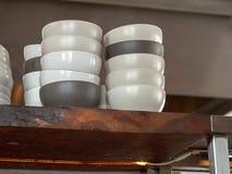 Pila de cuencos de cerámica blancos y negros que se sientan en un estante del restaurante foto de archivo libre de regalías