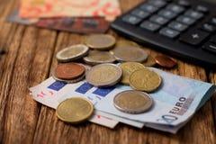 Pila de cuentas y de monedas euro más dos tarjetas y calculadoras de crédito Imagen de archivo libre de regalías