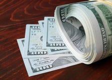 Pila de 100 dólares de EE. UU. de billetes de banco en fondo de madera Foto de archivo