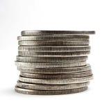 Pila de dólares y de monedas Imagenes de archivo
