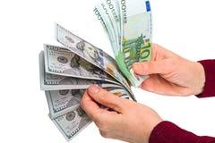 Pila de 100 dólares y euros en sus manos Imagen de archivo
