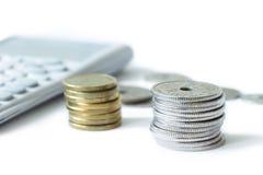 Pila de dinero con la calculadora aislada en el fondo blanco fotos de archivo
