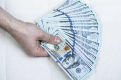 Pila de dinero a disposición en un fondo blanco Imagen de archivo libre de regalías