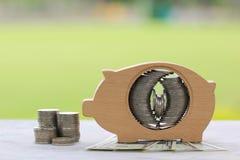 Pila de dinero de las monedas en madera de la hucha en backgro verde natural imagenes de archivo