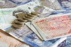 Pila de dinero y de gbp británico apilado de la libra esterlina de las monedas fotografía de archivo libre de regalías
