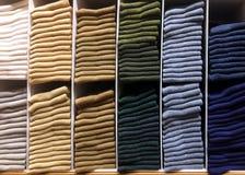 Pila de diversa ropa del color en estante Foto de archivo