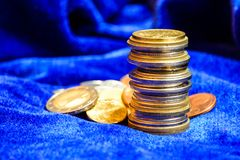 Pila de diversas monedas europeas en fondo azul del terciopelo Cierre para arriba imagen de archivo