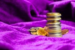 Pila de diversas monedas europeas en fondo púrpura del terciopelo Cierre para arriba foto de archivo