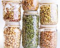 Pila de diversas semillas del brote que crecen en un tarro de cristal Foto de archivo