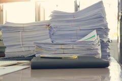 Pila de documentos inacabados en el escritorio de oficina Foto de archivo