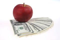 Pila de endechas de los dólares cerca de una manzana foto de archivo libre de regalías