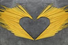 Pila de espaguetis largos amarillos crudos en un viejo fondo de madera Copie el espacio fotografía de archivo libre de regalías