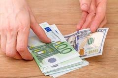 Pila de euros y de 100 dólares Imagen de archivo libre de regalías